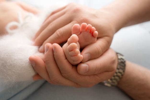 Mains des parents. les jambes du nouveau-né entre les mains de maman et papa. les jambes de bébé dans ses mains. photos de mains en noir et blanc. photo de haute qualité