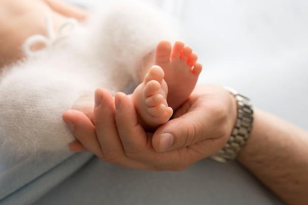 Mains des parents. les jambes, les pieds du nouveau-né entre les mains de maman et papa. photo de haute qualité