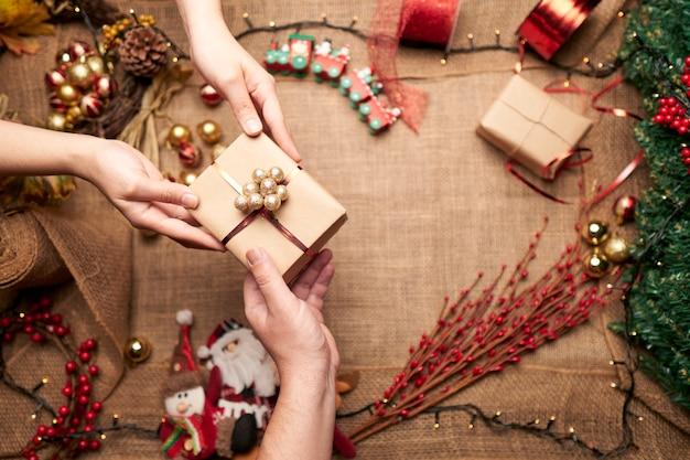 Mains partageant une boîte cadeau pour noël