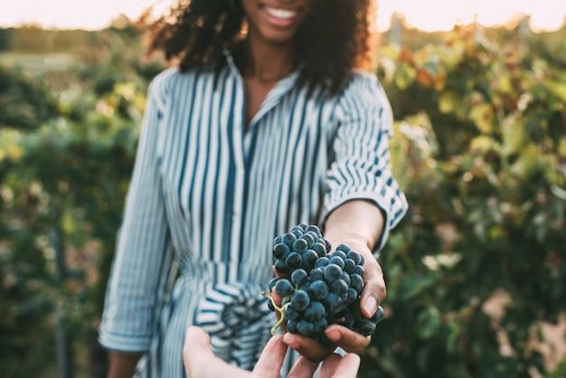 Mains partageant une grappe de raisin avec une femme floue heureuse