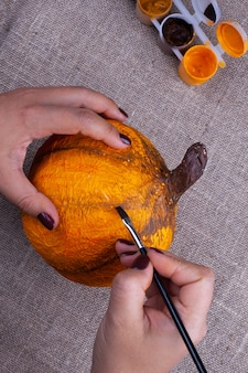 Mains peignent une citrouille en papier mâché maison en orange pour halloween, un passe-temps pour les enfants