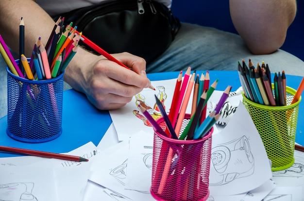 Les mains peignent le coloriage à la table des enfants