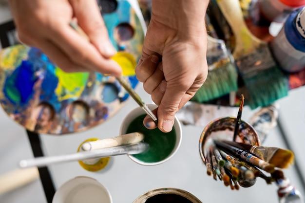 Mains de peintre tenant un pinceau sur un verre d'eau tout en nettoyant et en séchant les poils avant le travail