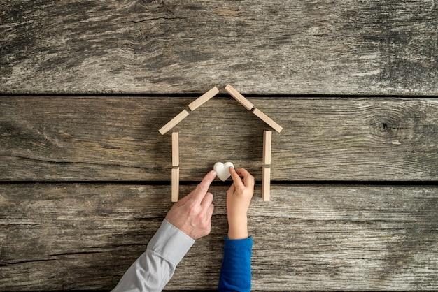 Mains d'un père et d'un fils à l'intérieur du cadre d'une maison tenant un coeur sur un fond en bois rustique.