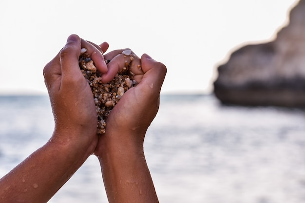 Mains d'une personne noire saisissant des pierres en forme de coeur