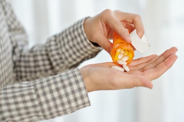 Mains de la personne prenant une dose quotidienne de pilules