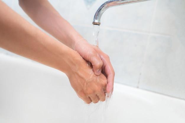Les mains de la personne se lavent avec de l'eau dans la salle de bain