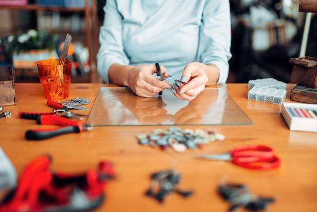 Mains de personne de sexe féminin avec des ciseaux, des bijoux faits à la main. couture, fabrication de bijouterie