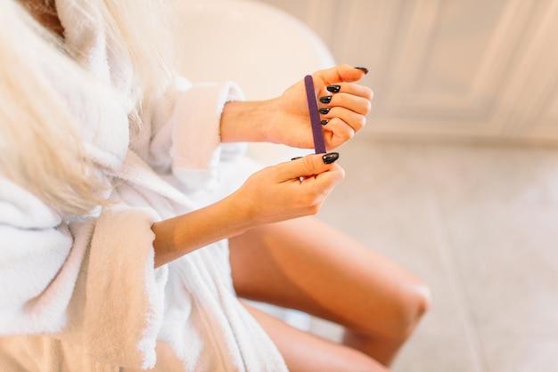 Mains de personne de sexe féminin avec lime à ongles, manucure