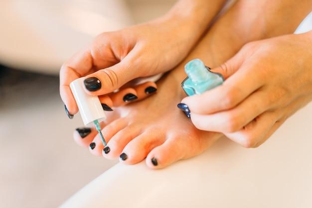 Mains de personne de sexe féminin avec vernis à ongles, pédicure