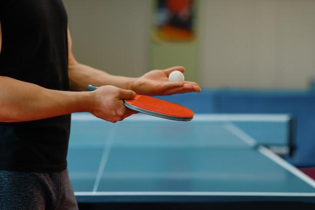Mains de personne de sexe masculin avec raquette et balle de ping-pong, entraînement à l'intérieur. homme en tenue de sport debout à table avec filet, entraînement au club de tennis de table