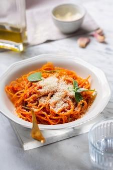 Les mains d'une personne sont saupoudrées de pâtes au parmesan à la sauce tomate dans une assiette de forme géométrique avec une fourchette. au fond, une bouteille d'huile d'olive et d'ail