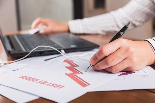 Les mains de la personne travaillant sur un ordinateur portable et des graphiques statistiques