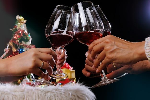 Mains de personnes de célébration de noël ou du nouvel an avec des lunettes de cristal