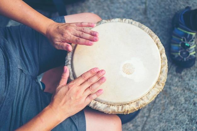 Mains de personnes jouant de la musique à la batterie de djembe, image de filtre vintage