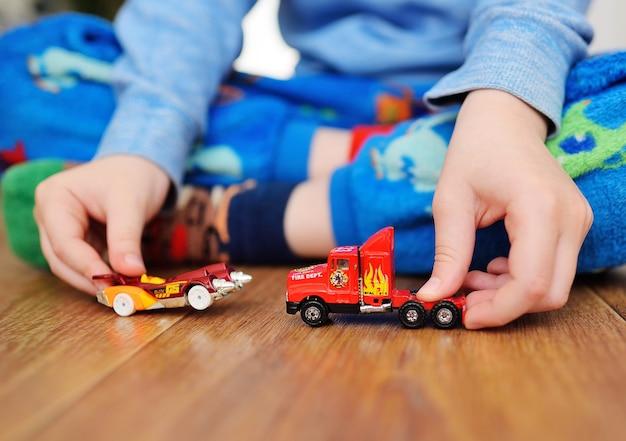 Mains d'un petit garçon en gros plan avec des petites voitures. enfance, jeu, développement
