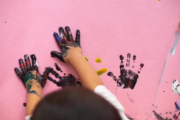 Mains d'un petit garçon peignant à l'aquarelle sur une feuille de papier rose. petit garçon avec un pinceau et de la peinture.