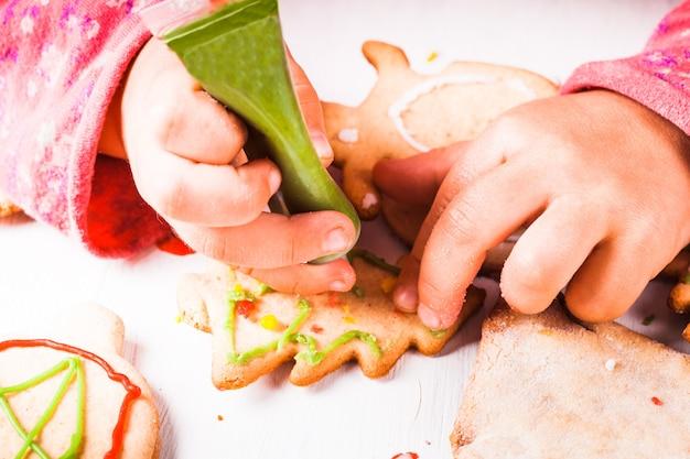 Mains de petite fille, qui dessine sur des biscuits de pain d'épice