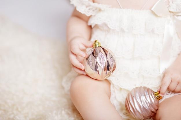 Mains de petite fille tenant un jouet de sapin