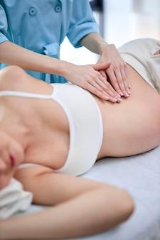Mains de physiothérapeute et ostéopathe donnant un massage professionnel à la future maman
