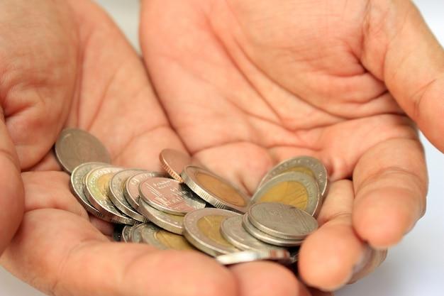 Mains avec des pièces de monnaie thaïlandaises