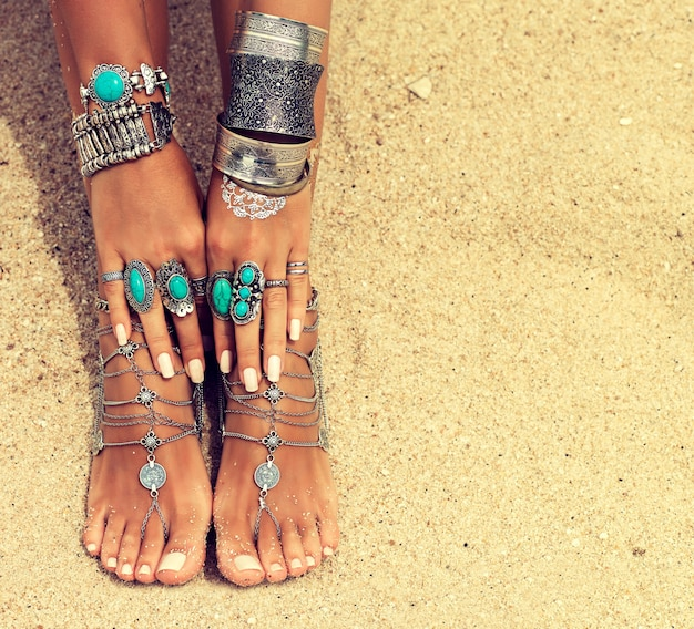 Les mains et les pieds bronzés de la femme avec une manucure et une pédicure blanches soignées décorées par des bracelets et des bagues en argent de style boho détente sur la plage tropicale