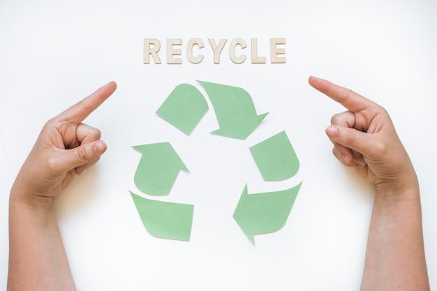 Mains pointant au mot de recyclage avec logo