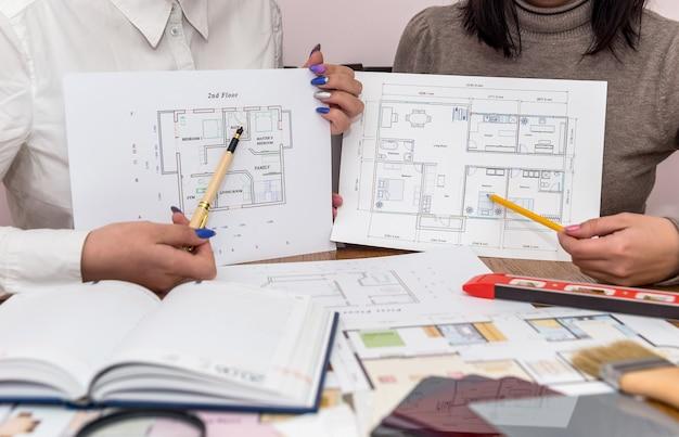 Mains pointant sur des modèles de maison, travail d'équipe de l'architecte