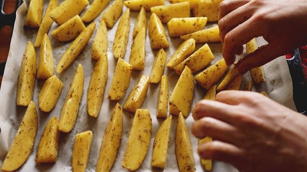 Mains - pommes de terre crues tranchées sur une plaque à pâtisserie avec des épices et du romarin, vue de dessus, copiez l'espace