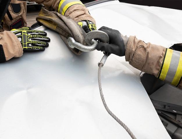 Les mains des pompiers fixant des crochets avec des élingues