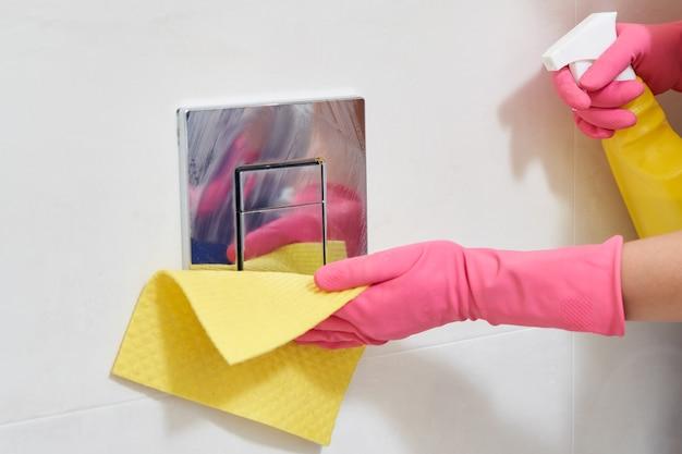Mains portant des gants de protection en caoutchouc nettoyant le bouton de chasse d'eau. concept de désinfection