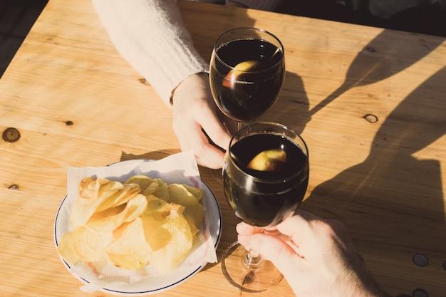 Mains portant un toast sur une table en bois avec une assiette de croustilles.