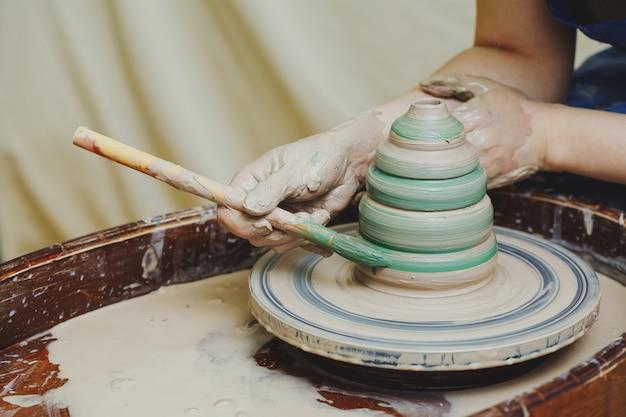 Mains sur potier. artisan artiste peinture pot avec pinceau