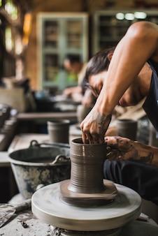Mains de potier closeup façonner l'argile molle pour faire un pot en terre