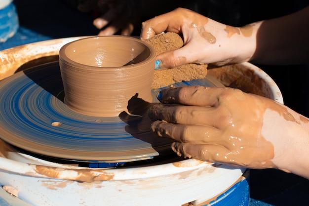 Mains d'un potier, créant un pot en terre sur le cercle