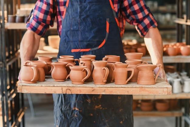 Mains de potier mâle tenant un plateau avec des pots en céramique au four dans la poterie.