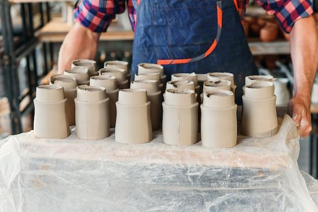 Mains de potier mâle tenant un plateau avec des pots en céramique dans la poterie.