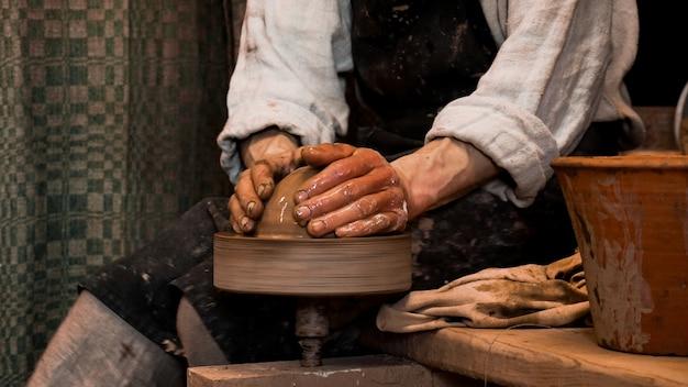 Mains de potier travaillant dans l'argile sur le tour de potier