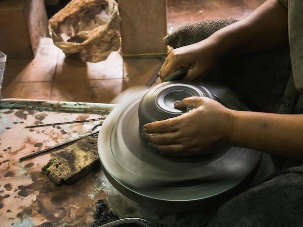 Les mains de potter façonnant de l'argile molle pour faire un pot en terre
