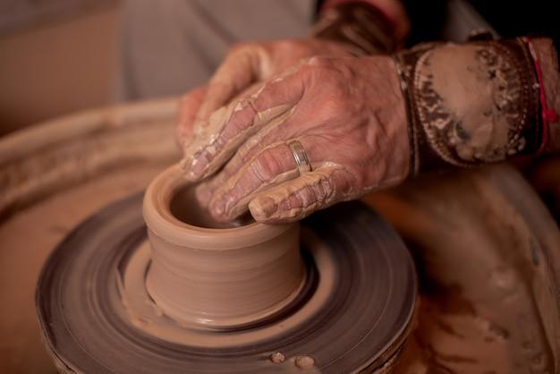 Les mains de potter travaillent avec de l'argile, ce qui en fait un produit.