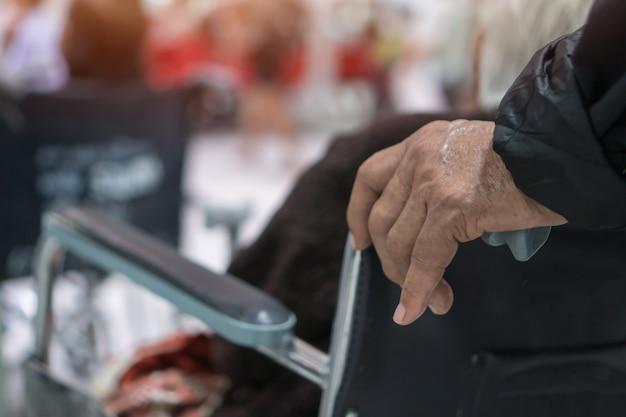 Mains poussant un patient âgé handicapé assis en fauteuil roulant, thérapie de services d'attente de docteur en clinique hospitalière. fauteuil roulant est une chaise avec des roues, utilisé lors de la marche difficile impossible à la maladie
