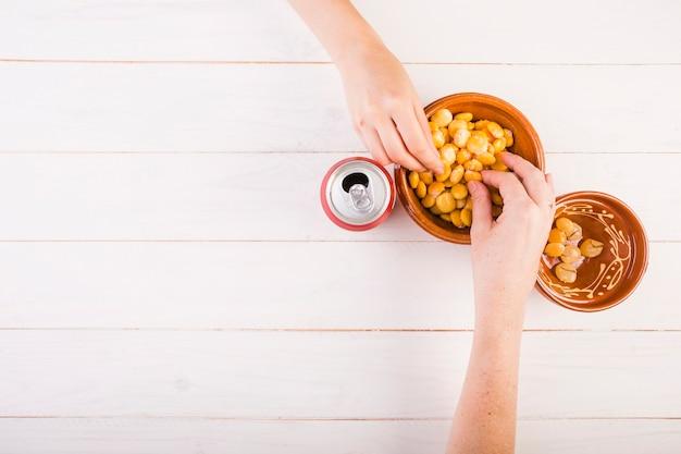 Mains prenant des haricots du bol sur la table