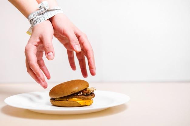 Les mains prennent un hamburger, les mains attachées au centimètre, la violation du régime alimentaire, les mains atteignant un hamburger qui se trouve sur une assiette sur un fond blanc