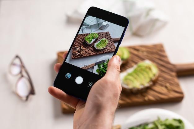 Les mains prennent des photos sur smartphone de deux beaux sandwichs à la crème sure et à l'avocat en bonne santé