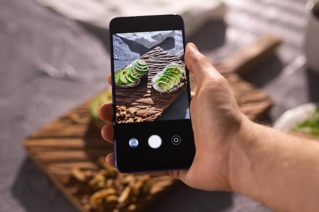 Les mains prennent des photos sur smartphone de deux beaux sandwichs à la crème sure et à l'avocat