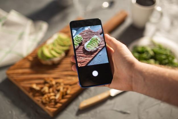 Les mains prennent des photos sur le smartphone de deux beaux sandwichs sains à la crème sure et à l'avocat allongés à bord sur la table. concept de médias sociaux et de nourriture