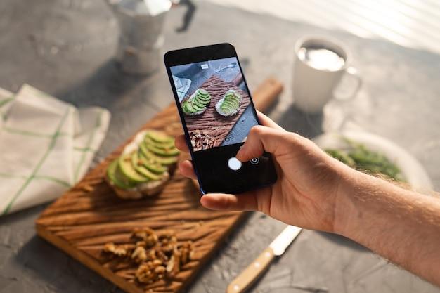 Les mains prennent des photos sur le smartphone de deux beaux sandwichs sains à la crème sure et à l'avocat allongés