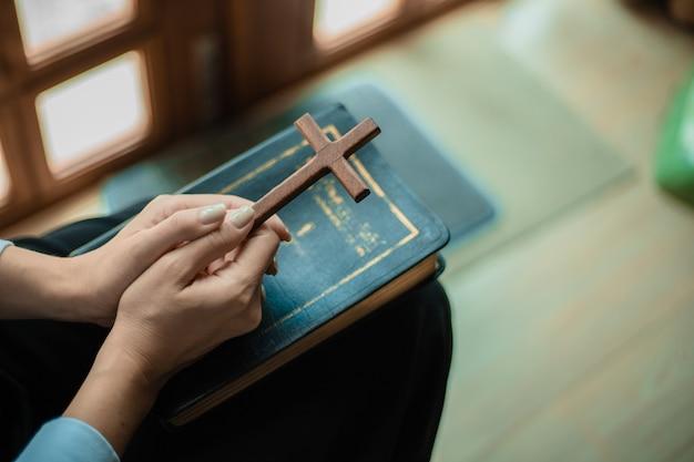 Les mains prient avec la bible et la croix en bois.