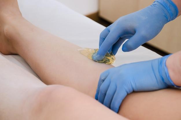 Les mains professionnelles de l'employé du salon dans des gants en latex bleu provoquent une pâte de sucre pour l'épilation sur les jambes féminines du client