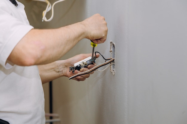 Mains professionnelles lors du montage du connecteur de prises électriques installé dans le placoplâtre de plaques de plâtre